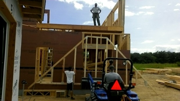 Creative carpentry: lifting a roof truss with a tractor.