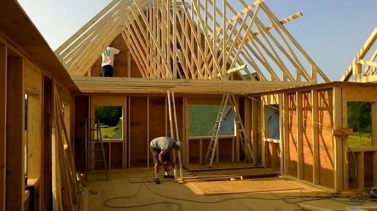 Colin braces the trusses while Carson and Terry hold the gable end steady.