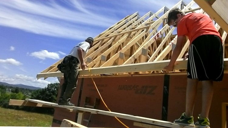 Terry and Turner on the scaffold attach a nailer across the truss bottoms to support the sheathing.