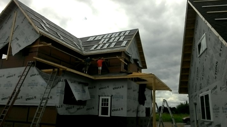 Progress on the shed roof, and bags of shingles on the gable roof ready to go.