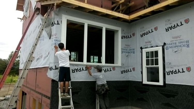 Carson and Terry nail a window in place.