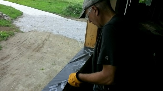 Colin sticks an Ice & Water Shield barrier on the sill. (It folds over and down the outside wall.)