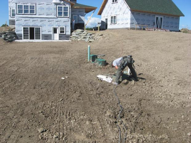The conduit runs mostly underground from the house to the septic. Cables are laid out behind Terry.