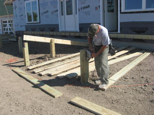 Terry notches a post. Lots of joist hangers on the ledger behind him.