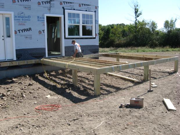 Terry installs joists for the future screen porch, which will anchor the wraparound.