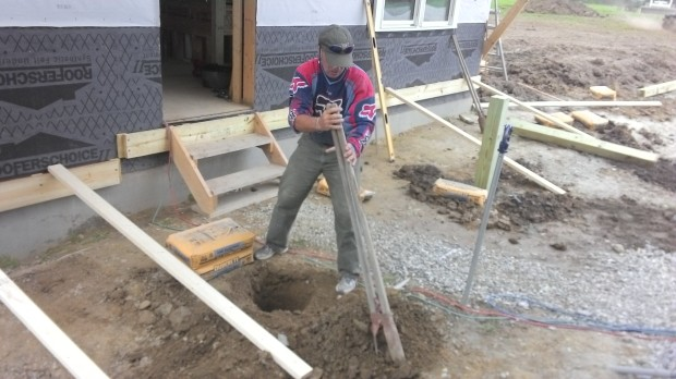 Digging a posthole with a posthole digger.