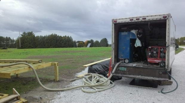 Unloading cellulose from the Bugbee Insulation truck into a vacuum hose. Their generator is very loud.