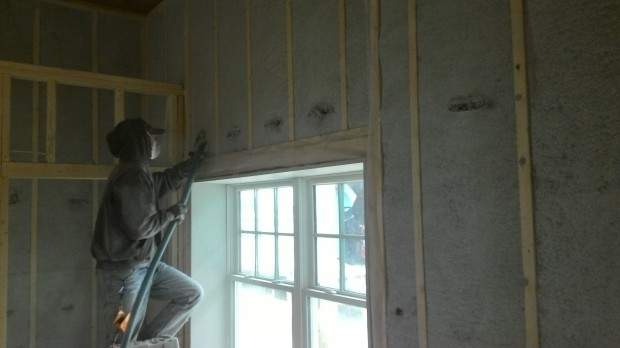 The insulation crew blows cellulose into the walls... wearing much-needed face and skin protection.