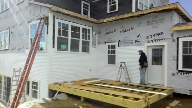 Walk-out basement and grill porch siding in progress. Colin checks alignment.
