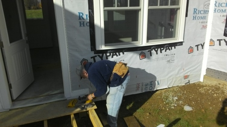 Colin fusses with the J-channels so they'll trim out the siding just right.