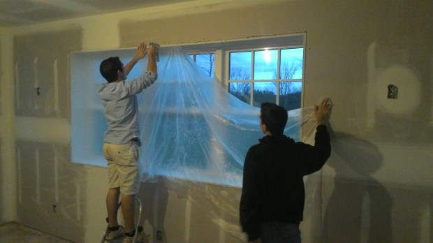 Carson and Cole prep a living-room window.