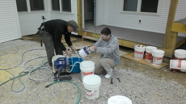Terry and Nat prepare the sprayer for ceiling paint.