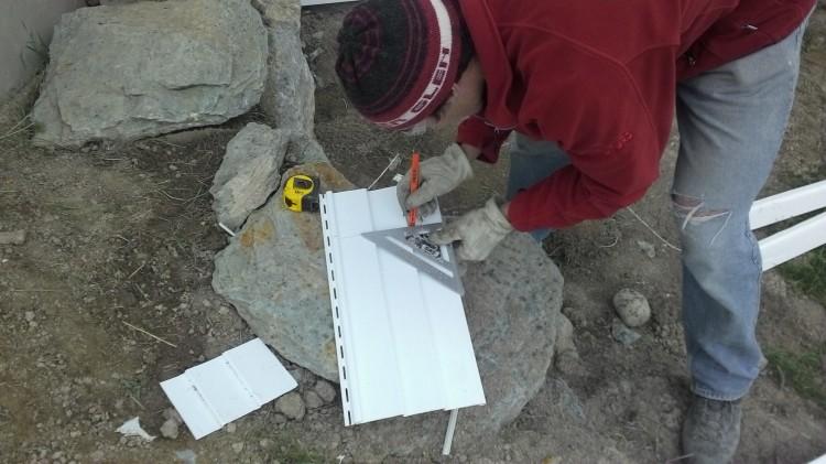 Marking a trim line on a piece of siding.