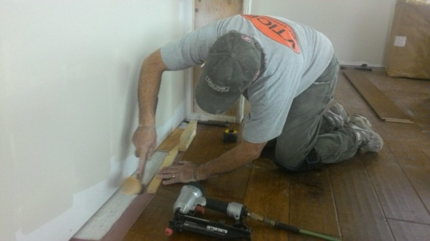 Resourceful: Terry uses a wedge of lumber to squeeze a floorboard into place near the wall.