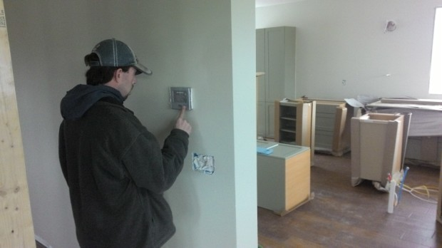 Rob from the HVAC contractor programs the thermostat.
