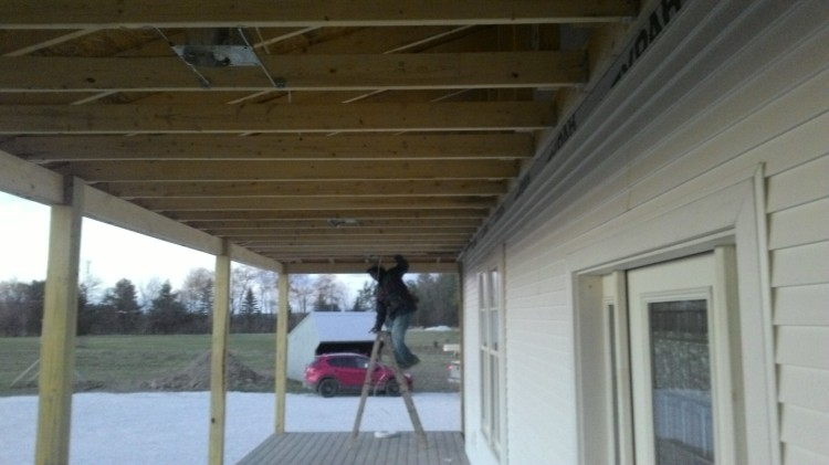 Colin installs lighting cans. Eventually we'll hide all the roof joists with soffit.