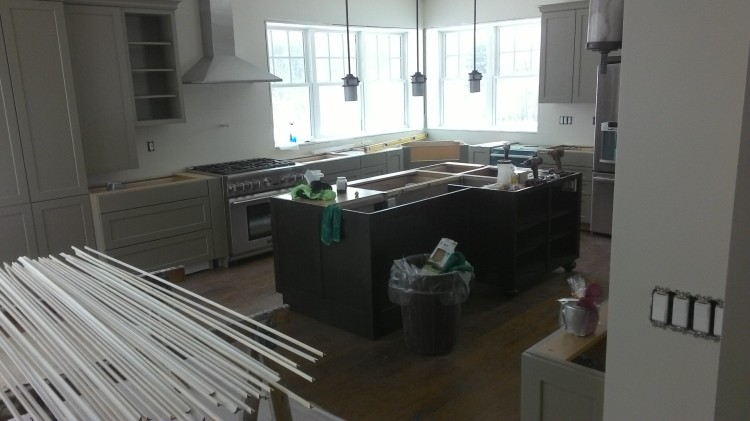Kitchen island pendants. In the foreground, trim pieces are primed and drying on the sawhorses.