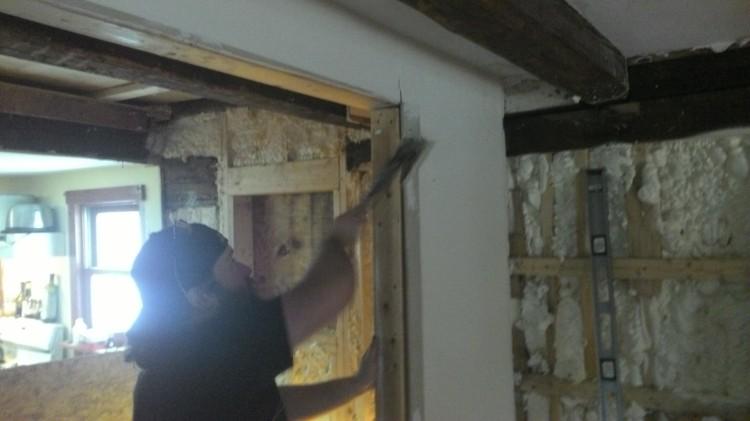 D.D. pries apart a closet door frame.