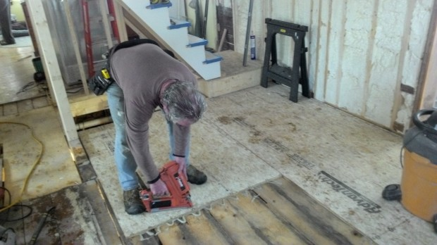 A mighty nail gun in the hands of Mark, as he installs the new subfloor.