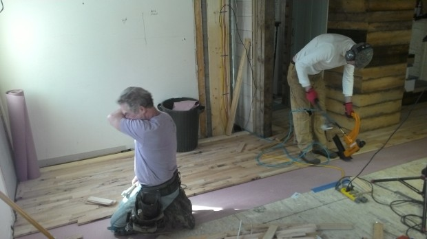 Mark and Hans at work in the living room. Hans operates the pneumatic flooring stapler.