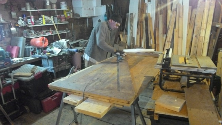 Working in the barn, Hans sands the Z-brace on the first door.