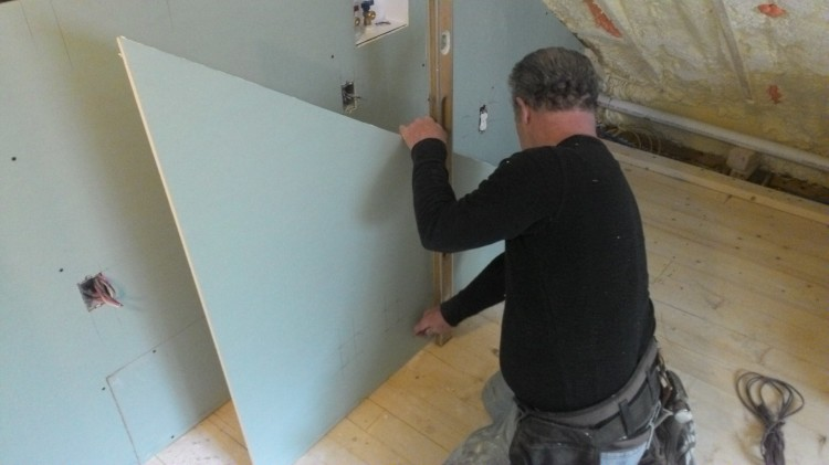 In preparation for a full-length cut, Mark scores a straight line using a level and a utility knife.