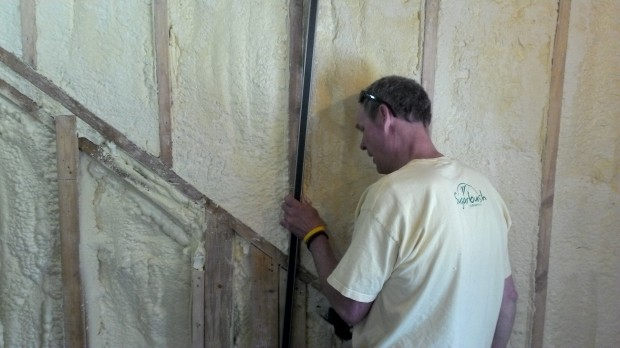 Hans checks an exterior wall for any out-of-planeness that would interfere with drywall.