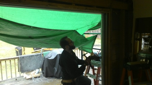 Julien opens up the dining room wall. A green tarp protects this opening from the elements.
