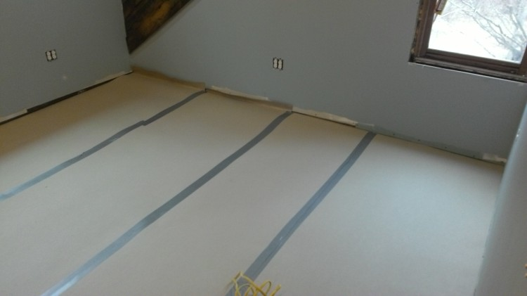 Master bedroom floor protected in preparation for foam insulation.