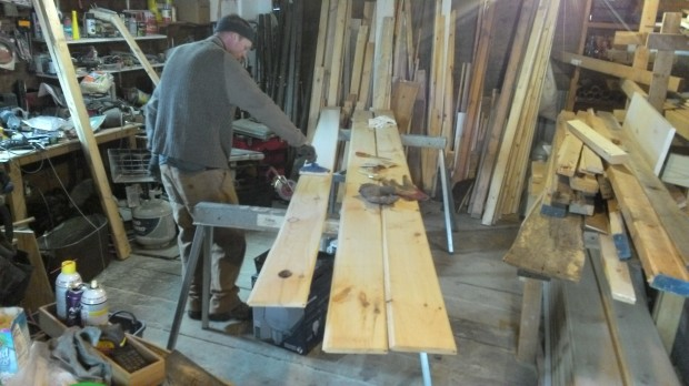 In the barn, Hans whitewashes a ceiling board.