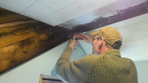 Hans uses a fine tool to cut a recess for the last row of ceiling boards.