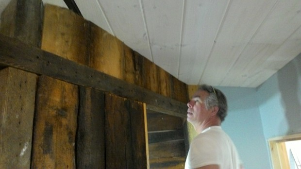 Mark admires his handiwork: a closed-up bathroom wall under a completed ceiling.