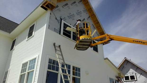 Maxed out the ladder... Terry installs siding from the lift.