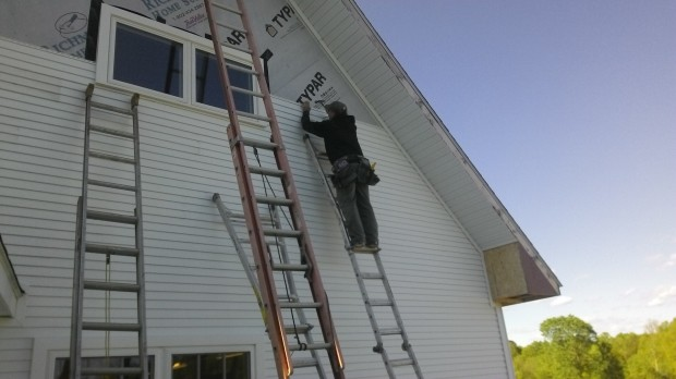 Terry adds more siding to the Barn's south gable end. Lots of ladders.