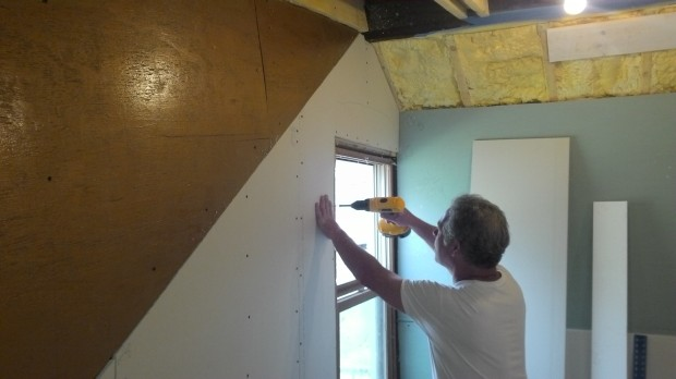 Screwing a drywall sheet to the studs behind it.
