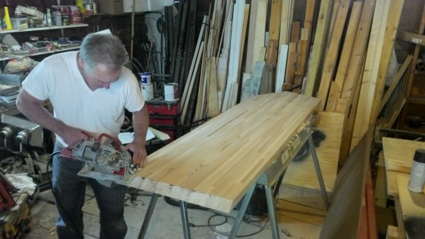 Mark cuts the counter, very carefully. (The cardboard template leans right of our saw table.)