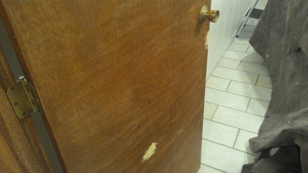 Wood putty dries solid to fill gashes in the door.