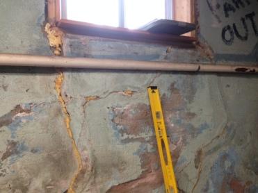 Cracks emanate from corners of window.